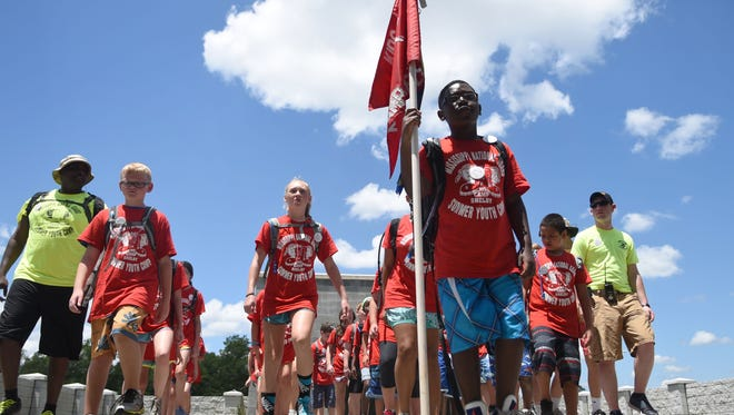 Anthony Gibson, 9, holds the flag for his group during the Kid's Annual Training summer camp at Camp Shelby's Combined Arms Collective Training Facility on Thursday. The week-long program had more than 100 kids age 9-12. The Mississippi National Guard military children learn routines that show what their parents experience while serving.