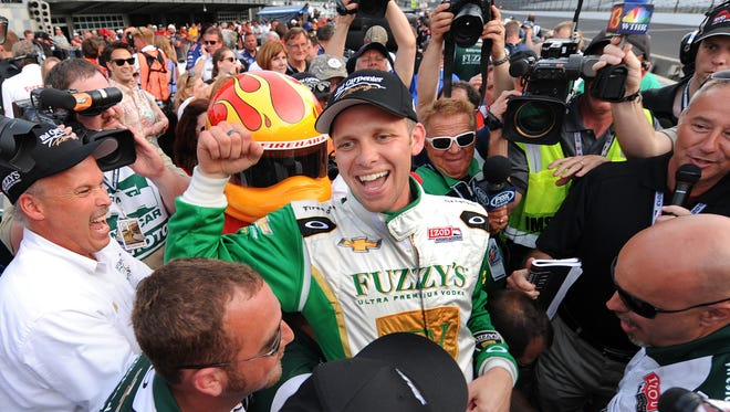 Driver Ed Carpenter screams in celebration moments before he is lifted in the air by his teammates after he won the pole at the Indianapolis Motor Speedway on Saturday, May 18, 2013.