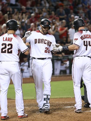 Diamondbacks JD Martinez (28) is greeted at home by teammate Paul Goldschmidt (44) and Jake Lamb (22) after hitting a three-run home run against Braves Matt Wisler (45) at Chase Field in Phoenix, Ariz. on July 24, 2017. It was the first home run for Martinez as a Diamondback.