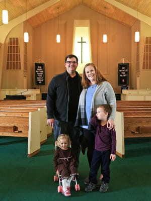 Matt Johnson and wife Clare with their children Kinsey, 2, and Mac, 5, in the Ridgewood Baptist Church in Pleasure Ridge Park. The affordable care act helped them when they moved to Kentucky from North Carolina.