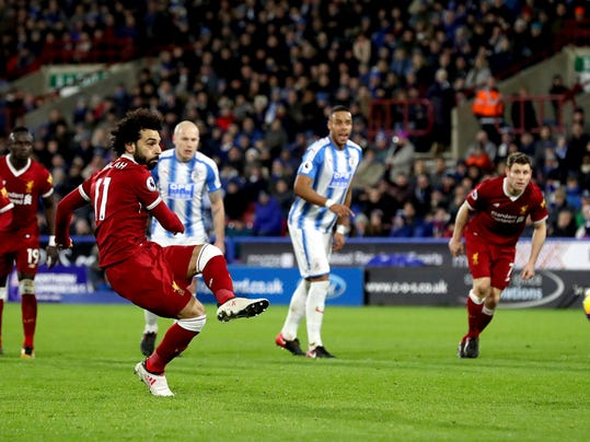 Liverpool's Mohamed Salah scores his side's third goal of the game from the penalty spot during their English Premier League soccer match against Huddersfield at the John Smith's Stadium, Huddersfield, England, Tuesday, Jan. 30, 2018. (Martin Rickett/PA via AP)