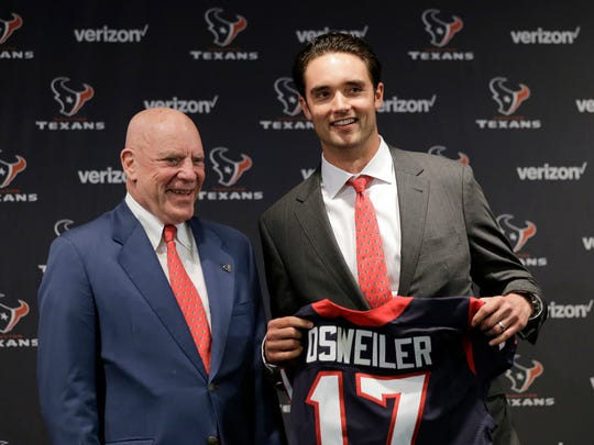 Houston Texans quarterback Brock Osweiler, right, holds his new jersey as he poses with owner Bob McNair during a news conference Thursday, March 10, 2016, in Houston. The Texans have filled their biggest need, starting free agency with a splash by snagging Osweiler from Denver. (AP Photo/David J. Phillip)