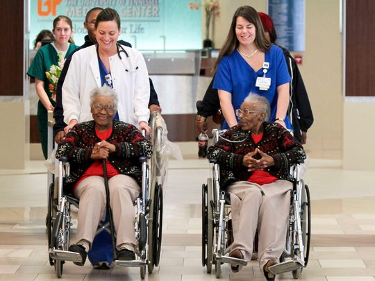 Love Kitchen co-founders Helen Ashe, front left, and Ellen Turner, front right, are wheeled out of the University of Tennessee Medical Center, by Rachel Hiyama, back left, and Kris Russell, back right, on March 4, 2011.