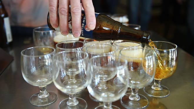 Samples of Fat Tire are poured on a tour of New Belgium Brewing in this file photo.