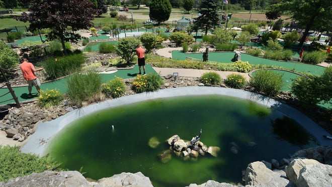 Adventure Zone owner Erick Friedman, 45, center left, and son Mason, 12, play on their newly-renovated minigolf course on Tuesday.
