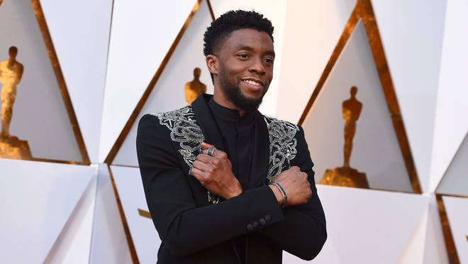 FILE - In this March 4, 2018 file photo, Chadwick Boseman arrives at the Oscars at the Dolby Theatre in Los Angeles.   Actor Chadwick Boseman, who played Black icons Jackie Robinson and James Brown before finding fame as the regal Black Panther in the Marvel cinematic universe, has died of cancer. His representative says Boseman died Friday, Aug. 28, 2020 in Los Angeles after a four-year battle with colon cancer. He was 43.