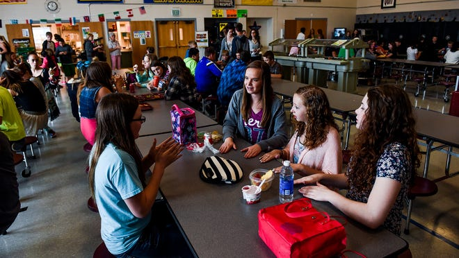 Clockwise from left, Sarah Keiss, Eva Meyer, Alexis Chismar and Caitlin Bernhardt play hand-clapping games during lunch Wednesday at Wellington Middle School.