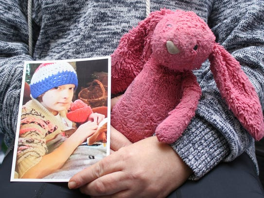 Michelle Langley holds a photo of her daughter Kenai