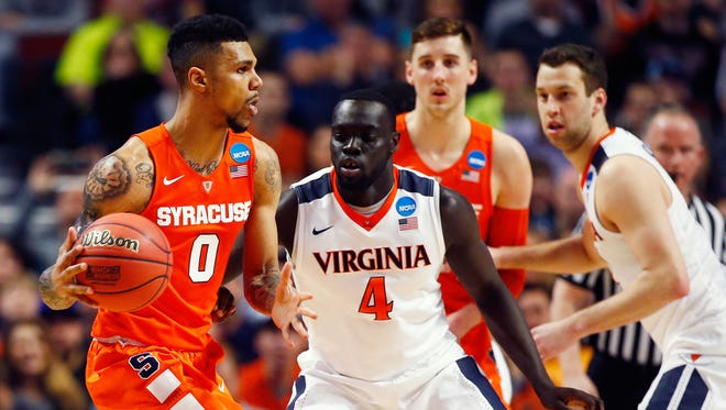 Syracuse's Michael Gbinije, left, drives against Marial Shayok of the Virginia Cavaliers at the 2016 NCAA Men's Basketball Tournament Midwest Regional Final at United Center in Chicago.