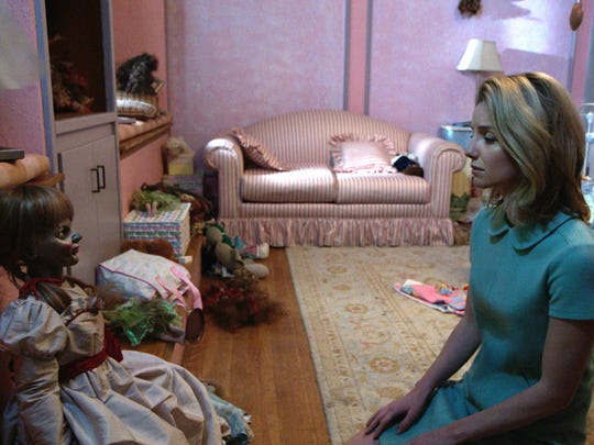"""Mia (right, Annabelle Wallis) sits with the Annabelle doll in the supernatural thriller """"Annabelle."""""""