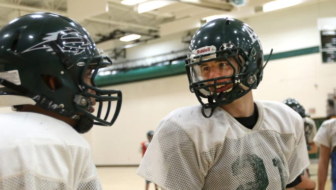 Adams-Friendship football player Joe Duty (21) laughs with another player during practice at Adams-Friendship High School, in Friendship, Wisconsin, Sept. 27, 2016.