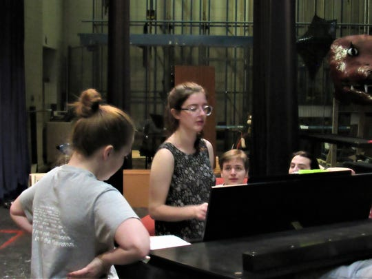 Kyla Johnson plays the piano, leading a group during rehearsal.