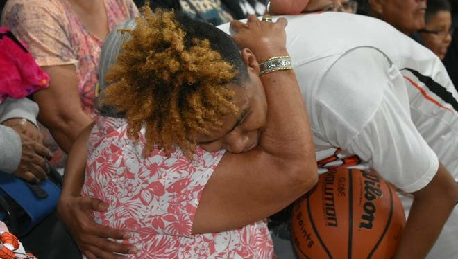 Robert Burries Jr. hugs his grandmother after scoring his 2,000th career point in a win over Florence.