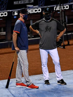 Red Sox manager Ron Roenicke, left, talks with Marlins manager Don Mattingly prior to their game Sept. 15 at Marlins Park. The Red Sox have had only one game altered by the coronavirus in this shortened MLB season.