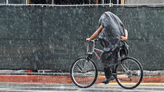 A cyclist tries to stay dry along Collins Ave. in Miami Beach, Fla. on May 25, 2018. Rain from Subtropical Storm Alberto is expected to will drench the Memorial Day weekend.