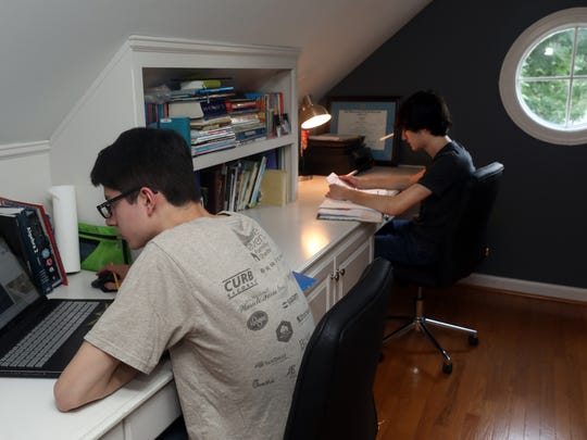 Joshua and Sam Cortez work on school assignments at