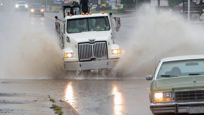 Vehicles travel along Towson Ave. near Fresno St. as rain continues to fall in Fort Smith on Tuesday.