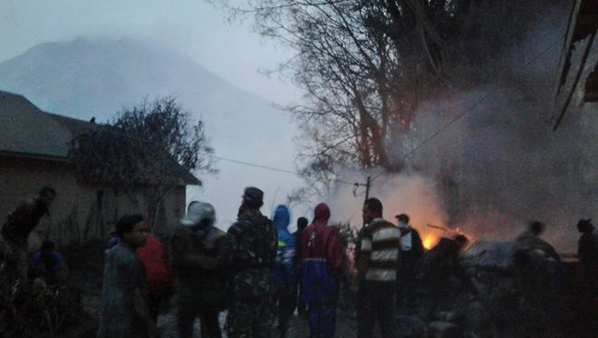 Villagers and rescuers stand near a burning tree after it was hit by pyroclastic flows from the eruption of Mount Sinabung, background, in Gamber, North Sumatra, Indonesia, Saturday, May 21, 2016.