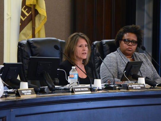 Battle Creek City Attorney Jill Steele, left, presents
