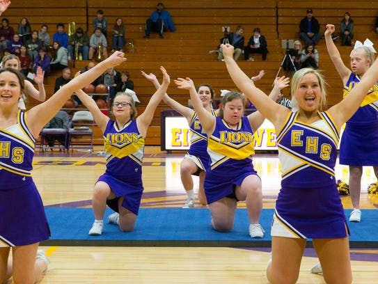 Sparkle cheerleaders Matilda Gillard (center left) and Victoria Loyo (center right) are framed by varsity cheerleaders Hailey Fortier (left) and Jodie Gurda (right) on Dec.12 at New Berlin Eisenhower High School in New Berlin. The Sparkle cheerleaders, who have learning disabilities, perform alongside the varsity cheerleaders at the school.