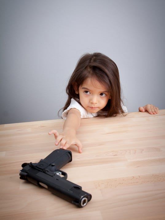 children play parent's gun. safety concept