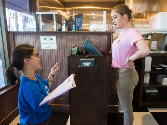Hostess trainer Kaley Nguyen, left, shows hostess Anastasia Cross how to greet diners during training at Metro Diner in North Naples on Tuesday, Jan. 24, 2017.