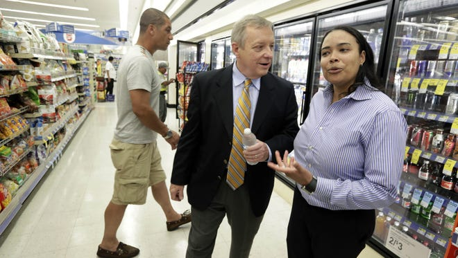U.S. Sen. Dick Durbin, D-Ill., center, talks to Walgreens store manager Crystal Buggs as he shops after a news conference Wednesday, Aug. 6, 2014, in Chicago. Durbin praised Walgreen, the nation's largest drugstore chain, for declining to pursue an overseas reorganization to trim its U.S. taxes.