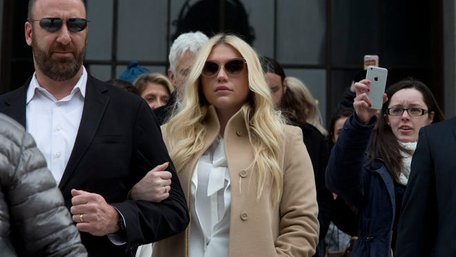 Pop star Kesha, center, leaves the Supreme Court in New York on Friday, Feb. 19, 2016.