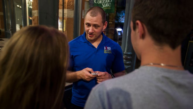 Bondi Beach Bar and Grill security manager Cory Esslinger checks patrons' IDs on Friday, June 15, 2018, in Old Town Fort Collins, Colo.