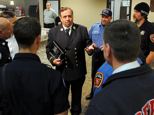 Ed Breen, a retired battalion chief with the Fire Department of New York, speaks with Sioux Falls Fire Rescue personnel after presenting the Carpet One store in Sioux Falls with a specially-designed shadowbox containing hallowed 9/11 steel from Ground Zero Monday, Dec. 1, 2015, at Carpet One in Sioux Falls. The Carpet One store in Sioux Falls received the award for their support of the Stephen Siller Tunnel to Towers Foundation's Building for America's Bravest program.