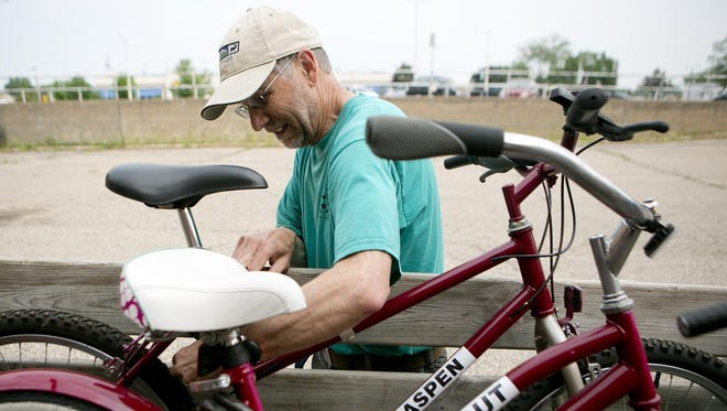 Clean Green Action's Joe Ancel works on loading bikes for River Riders Bike Share into a trailer at the former Daily Tribune building to be transported to Hotel Mead in Wisconsin Rapids on Tuesday, June 9.