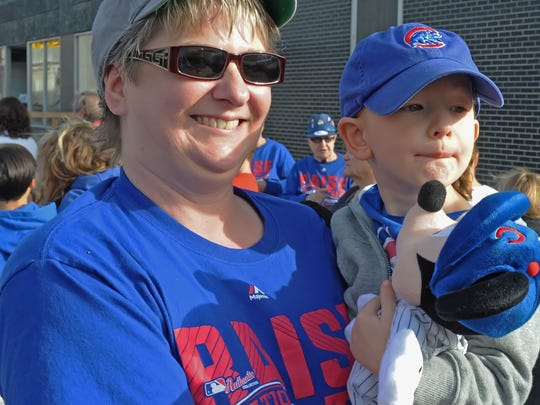 Dawn Smith and grandson Carter Mitchell-Woodrow watch as scores of loyal Chicago Cub fans flood Main Street in Lafayette Saturday afternoon to celebrate the Northsider's World Series comeback victory over the Cleveland Indians. For a gallery of Eric Schlene's images from the festivities, go to jconline.com.