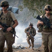 On Sept. 10, 2011, U.S. Army Pfc. Garrick Carlton, center, of Sacramento, Calif., hikes past burning rubbish to man a hilltop observation post along with fellow Pfc. Michael Tompkins, of Wadsworth, Ohio, left, and Pfc. Austin D'Amica, of San Diego, at Combat Outpost Monti in Kunar province, Afghanistan.