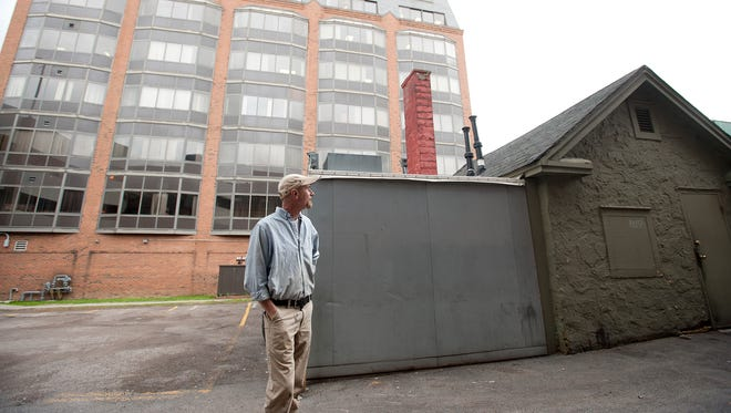 While standing in the alley behind Henry's Diner, Ron Wanamaker, a member of Burlington's design advisory board, discusses how important a sense of scale is to future development as he walks around Burlington on Wednesday evening.