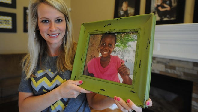 Amanda Larner, Fishers, holds a photo of her adopted daughter Rosalie, 6. Four Central Indiana women, mothers of adopted children in the Congo are waiting for exit letters from the Congo government to be able to bring their children to the United States.