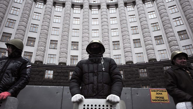 Anti-government protesters guard a government building in central Kiev on Feb. 25.