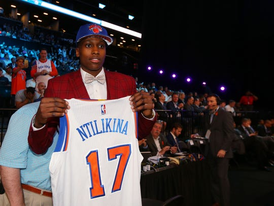 Frank Ntilikina of France holds up a team jersey after