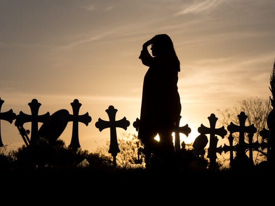 A woman visits a makeshift memorial in Sutherland Springs with 26 crosses honoring the victims killed in First Baptist Church on Nov. 7, 2017. The shooter killed 25 including a pregnant woman whose unborn child died.