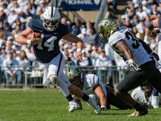 Penn State quarterback Sean Clifford eludes Purdue's Jonah Williams.