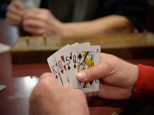 Bob Welle looks over his hand of cards that create multiple combinations of 15, a staple of cribbage scoring.