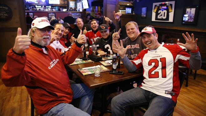 A contingent of Arizona Cardinals fans cheer for their team at Fitzgerald's Irish Pub on Saturday, Jan. 23, 2016, in downtown Charlotte, N.C.