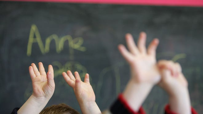 Children wave their hands in a classroom.