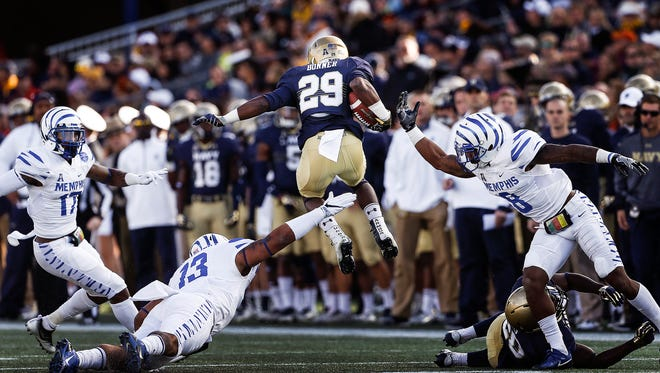 Navy running back Darryl Bonner (middle) leaps over the University of Memphis defense in the Midshipmen's 42-28 win over Memphis, which catapulted them to No. 1 in the AAC Power Rankings.