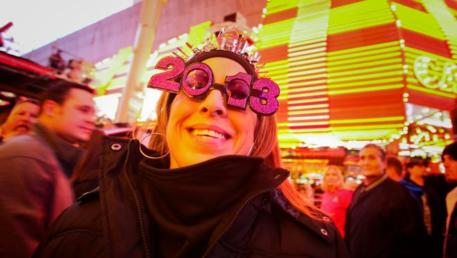 Carmen Zepeda, of Corpus Christi, Texas, shows off her 2013 New Year's Eve glasses at the Fremont Street Experience Downtown Countdown in Las Vegas on Dec. 31, 2012. On New Year's Eve night, some 340,000 people spending some $226 million, will crowd the Strip and downtown Fremont Street expecting to be entertained and for that reason, Las Vegas casino operators, event planners, tourism agencies and more have spent months planning ways to wow.