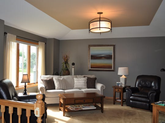 This photo shows an example of a tray ceiling painted in a solid color to reflect the warmth of the floor color in this newly designed space.