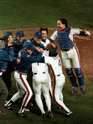New York Mets catcher Gary Carter, right, leaps on his teammates as they celebrate their 6-5 victory over the Boston Red Sox in the 10th inning of game six of the World Series at New York's Shea Stadium, Saturday, Oct. 25, 1986.  Boston was one out away from winning the championship before the Mets rallied for three runs and a victory.  The Mets went on to win the World Series in game 7.
