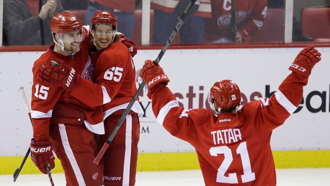 Detroit Red Wings defenseman Danny DeKeyser (65) is congratulated on his goal by center Riley Sheahan (15) and Tomas Tatar (21) of the Czech Republic during the third period of an NHL hockey game against the Vancouver Canucks in Detroit, Sunday, Nov. 30, 2014.