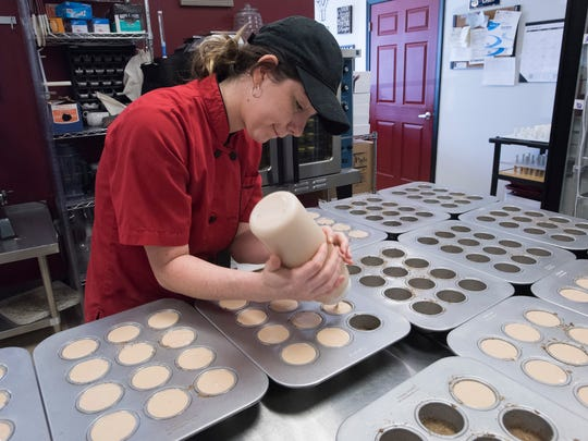 Kayla Parton fills cake molds with a signature Bushwacker Cheesecake batter mixture on Monday, Aug. 21, 2017, at Szotski's Cheesecakes. The business is owned by Jason Szot, who is retired from the Navy.
