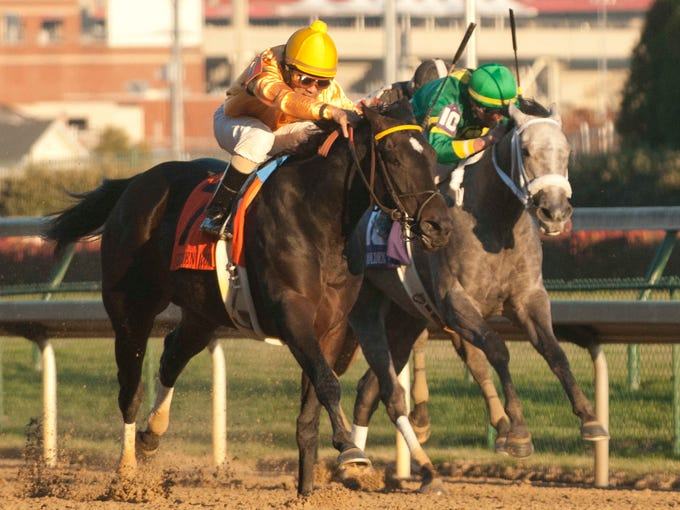 In the final stretch, jockey Shaun Bridgmohan, atop Vexed, left, battled with Corey Lanerie aboard Stonetastic, right. Vexed surged ahead en the end to win the 70th running of the Golden Rod Stakes. Nov. 30, 2013