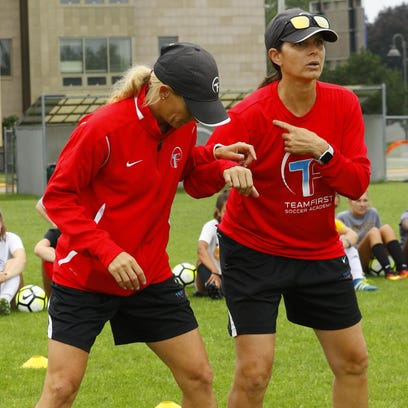 Former professional soccer players Mia Hamm, right,